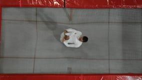 Взгляд от верхнего акробата гимнаста одетого в белизне выполняет прыжок кувырком на батуте видеоматериал