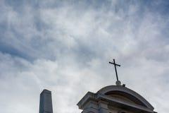 Взгляд от вниз к поднимающему вверх креста на частично облачном небе Backgr стоковая фотография rf
