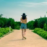 Взгляд от задней части девушки в желтом теле, шортах джинсовой ткани и шляпе, на дороге в зеленом цвете Стоковая Фотография