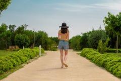 Взгляд от задней части девушки в желтом теле, шортах джинсовой ткани и шляпе, на дороге в зеленом цвете Стоковые Фотографии RF
