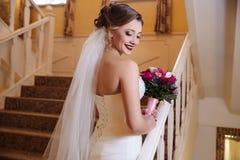 Взгляд от задней части красивой девушки в белом bridal платье свадьбы представляя на лестницах и смеяться над Стоковые Изображения