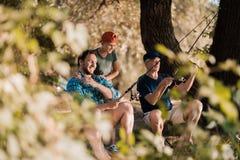 Взгляд от за деревьев Человек, его маленький сын и его пожилой отец удят для закручивать на речной берег Стоковые Фото
