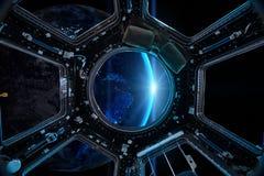Взгляд от иллюминатора космической станции на предпосылке земли Стоковое Изображение RF