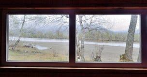 Взгляд от окна к реке на дождливый день Стоковая Фотография