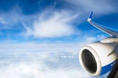 Взгляд от окна самолета к крылу и небу двигателя заволакивает Стоковые Фото