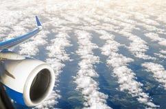 Взгляд от отсека пассажира иллюминатора к двигателю воздушных судн, под облаками земли гребней, гребет Стоковое фото RF