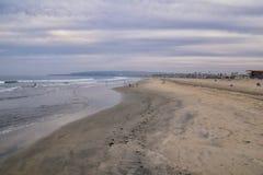 Взгляд от пляжа миссии в Сан-Диего, пристаней, молы и песка, вокруг серферов, включая предупредительные знаки, пальмы, волны, уте стоковые фотографии rf