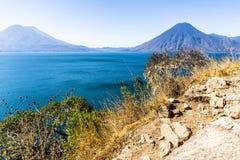 Взгляд от точки зрения clifftop через озеро Atitlan к вулканам, Гватемалу стоковое изображение rf