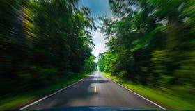 Взгляд от фронта голубого автомобиля на дороге асфальта и нерезкости движения скорости на шоссе в лете с зеленым лесом деревьев Стоковая Фотография