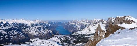 Взгляд панорамы ландшафта горы зимы с озером бирюзы и окружая снег-покрытыми пиками Стоковое Фото