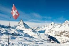Взгляд панорамы Маттерхорна и швейцарского флага Стоковая Фотография