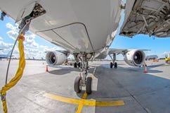 Взгляд переднего шасси, крыла и большого двигателя воздушных судн в месте для стоянки на авиапорте, наземном силовом кабеле Стоковые Фото