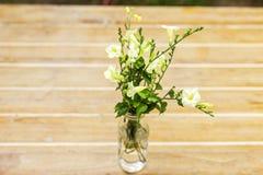 Взгляд перспективы белых цветков в стеклянной бутылке на деревянных животиках Стоковые Изображения RF