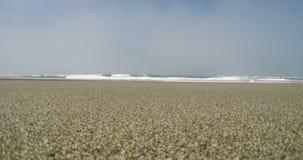 Взгляд песка ровный океанских волн и неба overcast видеоматериал
