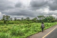 Взгляд пожилого фермера женщины, идя на сторону дороги, типичный тропический ландшафт как предпосылка стоковое изображение rf