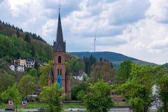 Взгляд протестантской церкви Hirschhorn Hesse, Германии с генератором ветротурбины на холме на заднем плане Стоковое Изображение RF