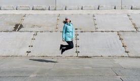 Взгляд профиля: девушка в синем пиджаке идя весело скакать на конкретную поверхность стоковое фото