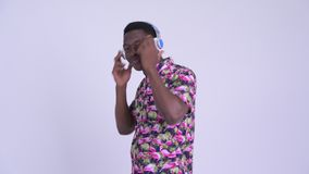 Взгляд профиля молодого счастливого африканского туристского человека слушая музыку и танцевать видеоматериал