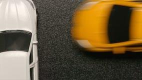 ВЗГЛЯД СВЕРХУ: АВТОМОБИЛЬНАЯ КАТАСТРОФА - желтый модельный автомобиль двигает к стороне белого автомобиля игрушки Стоковое фото RF