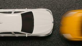 ВЗГЛЯД СВЕРХУ: АВТОМОБИЛЬНАЯ КАТАСТРОФА - желтый модельный автомобиль двигает к белому автомобилю игрушки Стоковое Фото