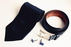 Взгляд сверху аксессуаров роскошных людей Черная связь шелка, черный кожаный пояс и запонки для манжет стоковая фотография