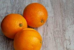 Взгляд сверху 3 апельсинов на белой деревянной предпосылке стоковые фото