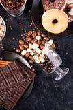 Взгляд сверху арахисов в шоколаде, разлитое на темной доске, рядом с таблетками шоколада, donuts, желтым сахарным песком и кофе Стоковая Фотография