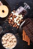 Взгляд сверху арахисов в шоколаде, разлитое на темной доске, рядом с таблетками шоколада, donuts, желтым сахарным песком и кофе Стоковое фото RF