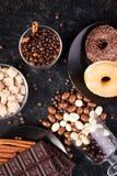 Взгляд сверху арахисов в шоколаде, разлитое на темной доске, рядом с таблетками шоколада, donuts, желтым сахарным песком и кофе Стоковые Фото