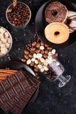 Взгляд сверху арахисов в шоколаде, разлитое на темной доске, рядом с таблетками шоколада, donuts, желтым сахарным песком и кофе Стоковое Изображение