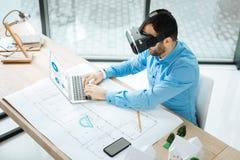 Взгляд сверху архитектора в шлемофоне VR работая на компьтер-книжке Стоковые Фото
