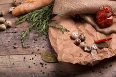 Взгляд сверху банка горячих красных перцев, пряного чеснока, яичек триперсток и розмаринового масла на скомканной бумажной и дере Стоковое Изображение