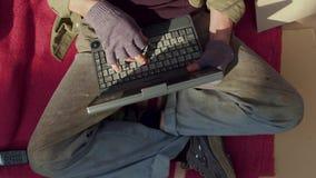 Взгляд сверху бездомного человека играя на компьтер-книжке сток-видео