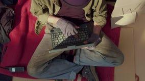 Взгляд сверху бездомного человека печатая на компьтер-книжке сток-видео