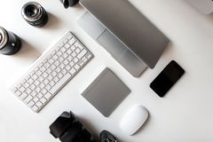 Взгляд сверху белого рабочего стола на котором лежат профессиональные объективы к камере, ноутбуку, клавиатуре, телефону, беспров стоковая фотография