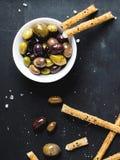 Взгляд сверху белого шара с черными и зелеными оливками и ручками хлеба стоковая фотография rf