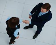 Взгляд сверху бизнесмена и коммерсантки тряся руки - гостеприимсво к делу Стоковое фото RF
