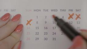 Взгляд сверху бизнес-леди вручает пересекать над ежемесячными датами назначения на повестке дня календаря - акции видеоматериалы