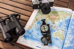 Взгляд сверху биноклей, компаса, photocamera и карты Стоковое фото RF