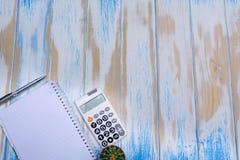 Взгляд сверху блокнота, ручки и калькулятора на backgr деревянного стола Стоковая Фотография