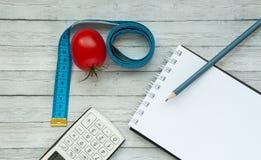 Взгляд сверху, блокнот и сочный томат с измеряя лентой, концепция уменьшения и здоровая еда стоковые фотографии rf