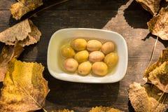 взгляд сверху больших зеленых оливок внутри желтых осенних листьев Стоковая Фотография