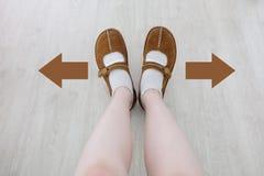 Взгляд сверху ботинка Брайна с различной стрелкой решения Брайна Пара стоять ног Направление ботинок идя на деревянном Стоковые Изображения