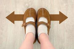 Взгляд сверху ботинка Брайна с различной стрелкой решения Брайна Пара стоять ног Направление ботинок идя на деревянном стоковая фотография rf