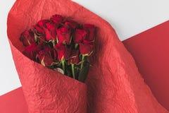 Взгляд сверху букета роз в красной упаковочной бумаге Стоковая Фотография