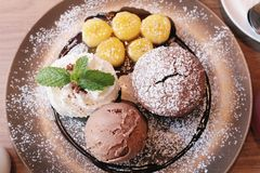 Взгляд сверху, булочка шоколада служило с мороженым шоколада, взбитой сливк и бананом, которое ` s покрыло с сиропом карамельки стоковое изображение