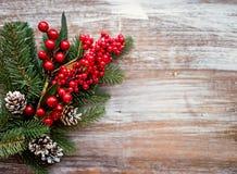 Взгляд сверху Ветви рождественских елок, красных ягод и рему на деревянной предпосылке установьте текст Стоковые Фотографии RF
