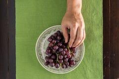 Взгляд сверху виноградины выбранной рукой в блюде стоковое изображение