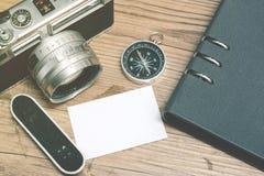 Взгляд сверху винтажной камеры, компас, surfboard и плановик записывают план на деревянном поле Стоковые Изображения