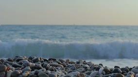 Взгляд сверху волн, пены и покрашенных камней каек пляжа сток-видео